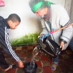 The marriage well-keeper Shareef Idrissi Saleh and his son Mohammed pour the special water in a bucket