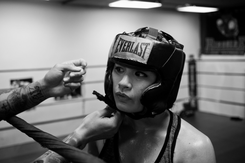 Casey Morton is fitted with a helmet by her full-time coach, Jairo Escobar, before sparring with another female boxer at World Class Boxing Gym in San Francisco, CA.