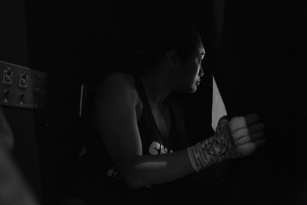 Casey apprehensively peeks through the curtain and scans the crowd as she waits for her name to be called by the announcer for her pro-debut fight.