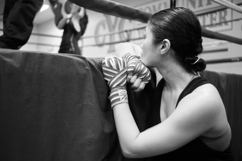 Casey takes some quiet time to rest and watch two young pupils practice sparring against one another in the ring at the Community Youth Center in Concord, CA.