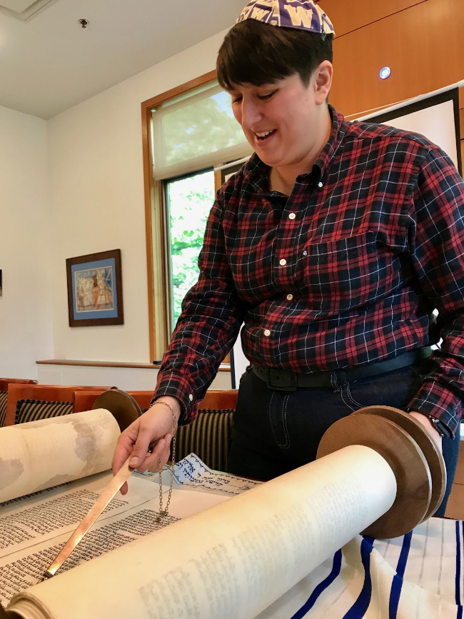 Rabbi Dana Benson smiles while reciting from an old Torah scroll at Hillel at the University of Washington in Seattle on Tuesday, May 16. While her rabbinical status is regarded in progressive denominations of Judaism, her authority is not upheld in an Orthodox synagogue because she is a woman. (Photo courtesy of Claire Butwinick)
